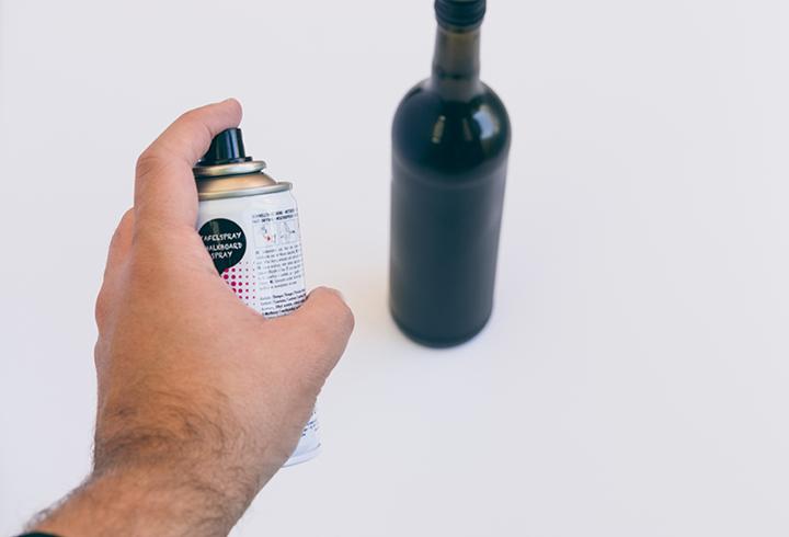 Adventskranz aus Flaschen selbermachen. Im ersten Schritt sprühst du die Flaschen mit dem Tafelspray an.