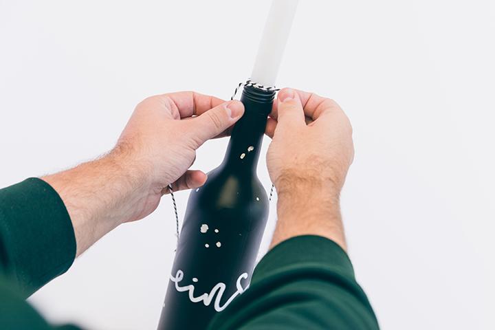 Adventskranz aus Flaschen selbermachen. Zum Schluss ein wenig Garn um den Flaschenhals wickeln.
